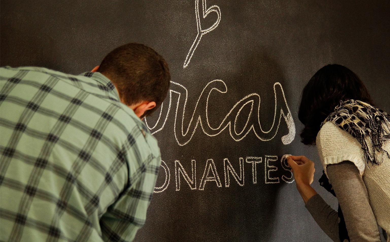 Nossa abertura foi especial, com a marca da websérie sendo desenhada na parede de quadro negro - Foto: Carol Lá Lach